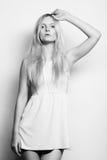 blonde Frau im weißen Kleid, das im Studio aufwirft Stockfotografie