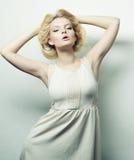 blonde Frau im weißen Kleid, das im Studio aufwirft Lizenzfreies Stockfoto