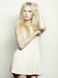 blonde Frau im weißen Kleid, das im Studio aufwirft Stockbild