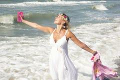 Blonde Frau im weißen Kleid durch den Ozean Lizenzfreies Stockbild