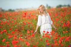 Blonde Frau im weißen Kleid gehend durch blühenden roten Fluss des Sommers Lizenzfreies Stockbild