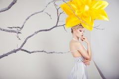 Blonde Frau im weißen Kleid mit großer gelber Blume Stockfotografie
