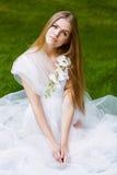 Blonde Frau im weißen Kleid mit Orchidee Lizenzfreie Stockbilder