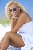 Blonde Frau im weißen Kleid u. in den Sonnenbrillen am Strand lizenzfreie stockfotografie