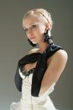 Blonde Frau im weißen Kleid und in den schwarzen Handschuhen Stockfotografie