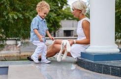 Blonde Frau im weißen Kleid und in ihrem netten kleinen Kind Lizenzfreies Stockfoto