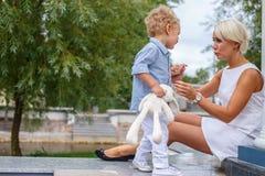 Blonde Frau im weißen Kleid und in ihrem netten kleinen Kind Stockbilder