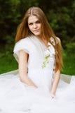 Blonde Frau im weißen Sitzen auf Natur Stockfotos