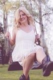 Blonde Frau im weißen Spitzekleid auf einem Schwingen Lizenzfreie Stockfotos