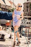 Blonde Frau im weißen transparenten Kleid und im Badeanzug, die auf Yacht steht Lizenzfreies Stockbild