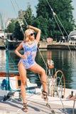 Blonde Frau im weißen transparenten Kleid und im Badeanzug, die auf Yacht steht Stockbild