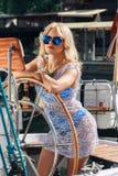 Blonde Frau im weißen transparenten Kleid und im Badeanzug, die auf Yacht steht Lizenzfreies Stockfoto