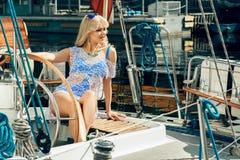 Blonde Frau im weißen transparenten Kleid und im Badeanzug, die auf Yacht steht Stockfotografie