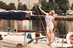 Blonde Frau im weißen transparenten Kleid und im Badeanzug, die auf Yacht steht Lizenzfreie Stockbilder