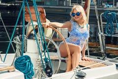 Blonde Frau im weißen transparenten Kleid und im Badeanzug, die auf Yacht steht Lizenzfreie Stockfotografie