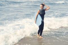 Blonde Frau im Wetsuit gehend aus dem Wasser heraus Stockbilder