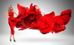 Blonde Frau im windigen roten Kleid Lizenzfreies Stockfoto