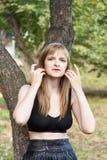 Blonde Frau korrigiert Haar Stockfoto