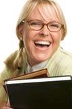 Blonde Frau lächelt u. trägt Stapel Bücher Stockbild
