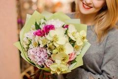 Blonde Frau lächelt und hält einen Blumenstrauß mit Orchideen, Rosen und Hortensie Stockbilder