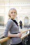 Blonde Frau lehnt sich auf dem Geländer Stockfotografie
