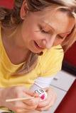 Blonde Frau malte ein lustiges Osterei Lizenzfreie Stockbilder