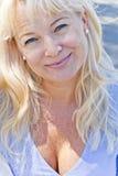 Blonde Frau mit blauen Augen am sonnigen Tag Stockbild