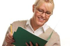 Blonde Frau mit Bleistift und Faltblatt Stockfotos