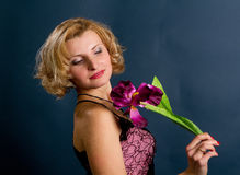 Blonde Frau mit Blume auf einem dunklen Hintergrund Stockbild