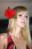 Blonde Frau mit Blume beim Haarträumen Stockbilder