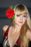 Blonde Frau mit Blume im Haar Stockbild
