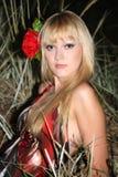 Blonde Frau mit Blume im Haar Stockfotografie