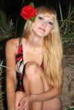 Blonde Frau mit Blume im Haarsitzen Stockfotografie