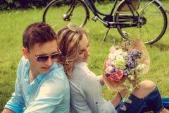 Blonde Frau mit Blumen und Mann in der Sonnenbrille Lizenzfreie Stockfotografie