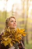 Blonde Frau mit Blumenstrauß von den Ahornblättern Lizenzfreies Stockbild