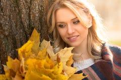 Blonde Frau mit Blumenstrauß von den Ahornblättern Stockfotos