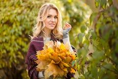Blonde Frau mit Blumenstrauß von den Ahornblättern Stockbild