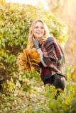 Blonde Frau mit Blumenstrauß von den Ahornblättern Stockbilder
