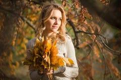 Blonde Frau mit Blumenstrauß von den Ahornblättern Lizenzfreie Stockfotos