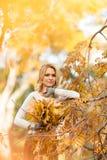 Blonde Frau mit Blumenstrauß von den Ahornblättern Stockfotografie