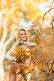 Blonde Frau mit Blumenstrauß von den Ahornblättern Lizenzfreie Stockbilder
