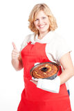blonde Frau mit bundt Kuchen und rotem Vorfeld Lizenzfreies Stockbild