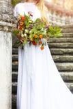 Blonde Frau mit dem Blumenstrauß, der in einem Hochzeitskleid aufwirft Abschluss oben Lizenzfreie Stockbilder