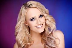 Blonde Frau mit dem gelockten Haar, das auf buntem Hintergrund aufwirft Stockbilder