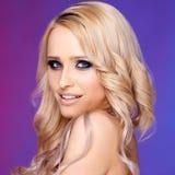 Blonde Frau mit dem gelockten Haar, das auf buntem Hintergrund aufwirft Stockfoto