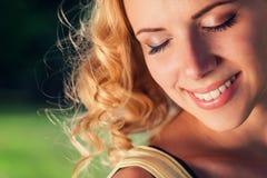 Blonde Frau mit dem gelockten Haar, geschlossene Augen Grüne Natur Lizenzfreie Stockfotos
