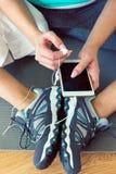 Blonde Frau mit dem intelligenten Telefon, stehend nach Turnhallentraining still Stockfotos