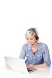 Blonde Frau mit dem Kopfhörer, der Laptop betrachtet Stockfoto