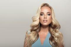 Blonde Frau mit dem langen gelockten schönen Haar Stockfotografie
