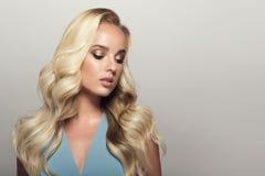 Blonde Frau mit dem langen gelockten schönen Haar Lizenzfreie Stockfotos